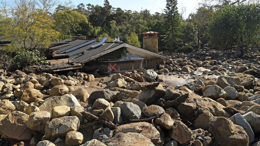 MONTECITO, CALIFORNIA JANUARY 10, 2018-A house sits among boulders and mud along Glen Oaks Drive in