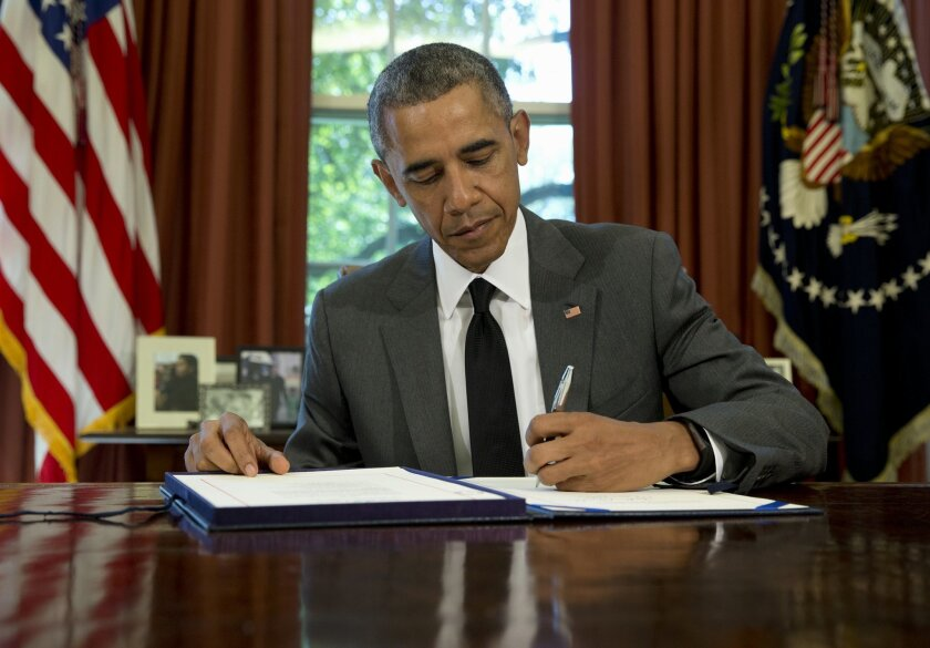 """President Barack Obama signs the three-month highway funding bill, Friday, July 31, 2015, in the Oval Office of the White House in Washington. The president said the U.S. government can't keep funding highway and transit projects """"by the seat of our pants."""" Obama's comments came as he signed a three-month bill to keep transportation money flowing to states. The patch is the 34th short-term transportation measure since 2009. (AP Photo/Carolyn Kaster)"""