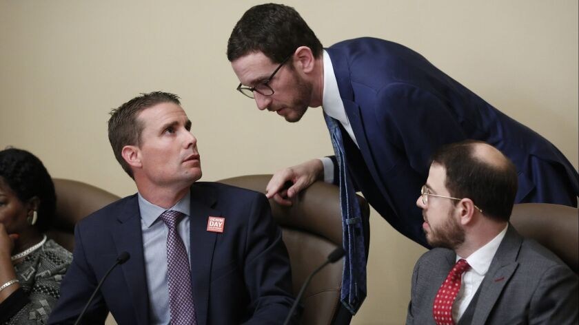 State Sen. Mike McGuire (D-Healdsburg), left, confers with State Sen. Scott Wiener (D-San Francisco), center, during a hearing Wednesday in Sacramento on their housing bills.