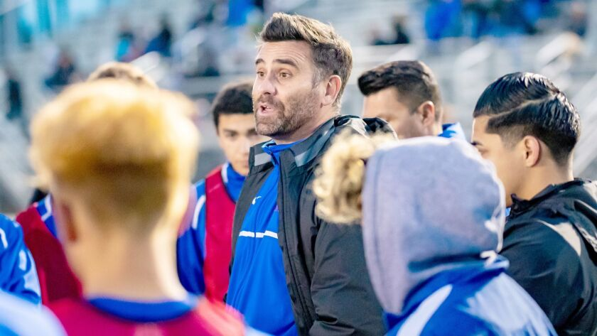 Coach Michael Jordan II talks to his boys varsity soccer players during Friday's CIF quarterfinals m