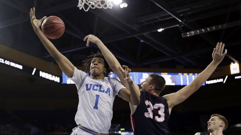 UCLA center Moses Brown, left, loses his grip on the ball as he is defended by Belmont center Nick Muszynski during the second half.