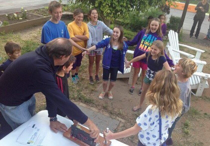 Fifth-graders Margo Lyons, Kennedy Snyder, Olivia Myers and friends make a human electric circuit with the help of parent volunteer Eric Korevaar.