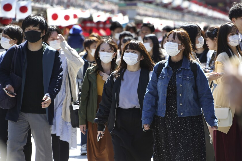 Visitors wearing face masks walk through Nakamise alley in Tokyo in March.