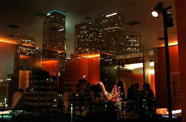 The downtown Los Angeles skyline is reflected in windows on the sixth floor of the Los Angeles Times Building as guests attend Bite Nite, a night with Jonathan Gold celebrating his 101 best L.A. restaurants.