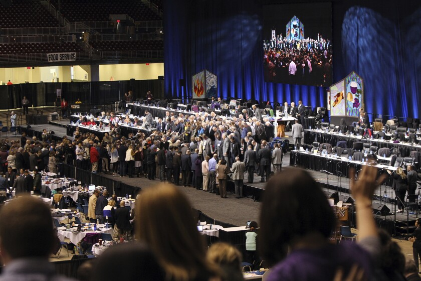 United Methodist bishops and delegates gather together to pray at the front of the stage before a key vote on church policies about homosexuality on Feb. 26, 2019, during the special session of the General Conference of The United Methodist Church, held in St. Louis, Mo. (Kit Doyle/Religion News Service via AP)