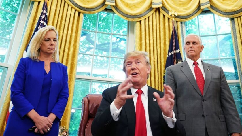 Homeland Security Secretary Kirstjen Nielsen and Vice President Mike Pence stand behind President Trump after he signed an executive order in the Oval Office on Wednesday to end the separation of migrant families at the border.