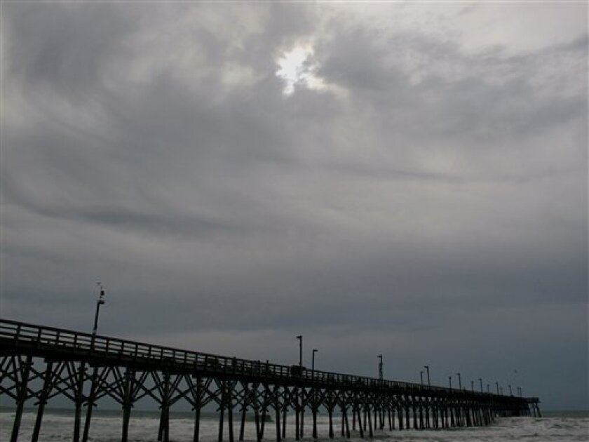 Clouds from the advancing rainbands of Hurricane Earl shroud the sun over the pier in Surf City, N.C. on Thursday, Sept. 2, 2010. (AP Photo/Bruce Smith)