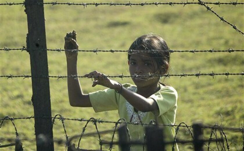 A girl stands behind a fence marking the Indian border with Bangladesh in Champakgachh village, about 25 kilometers (16 miles) from Siliguri, India, Thursday, Dec. 9, 2010. India's security forces routinely gun down cattle smugglers and other civilians crossing the border with Bangladesh despite sc