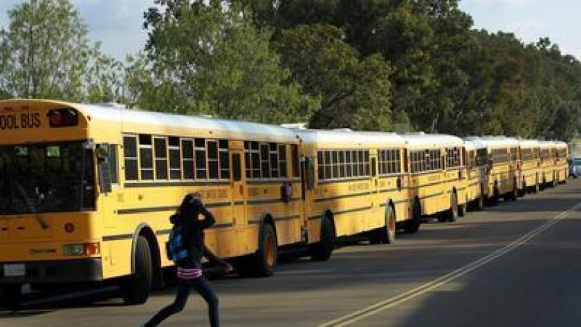 File art of school buses. Vista Unified is adjusting spending to close budget gaps.