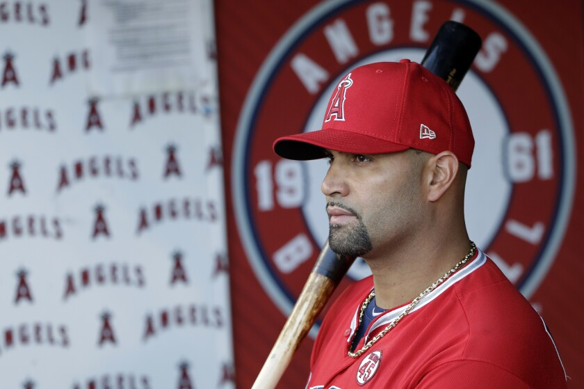 Angels' Albert Pujols holds a bat in the dugout before the start of a game.