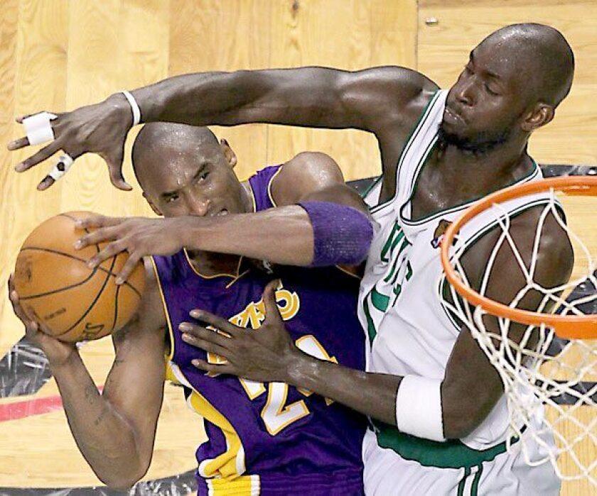 Celtics forward Kevin Garnett forces Lakers guard Kobe Bryant into a difficult shot.