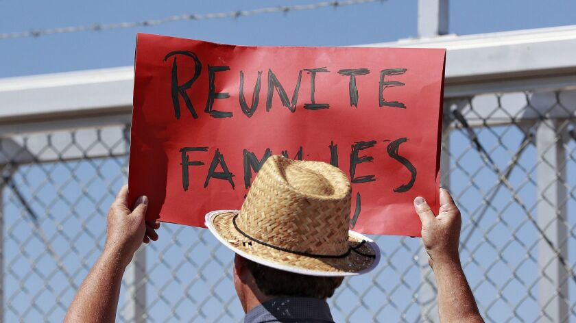A protester holds a sign outside a closed gate at the Port of Entry facility, Thursday, June 21, 201