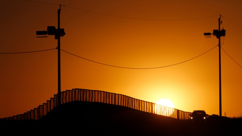 Sunset at the U.S.-Mexico border in Naco, Ariz., where a Border Patrol agents in his car keeps on activity.