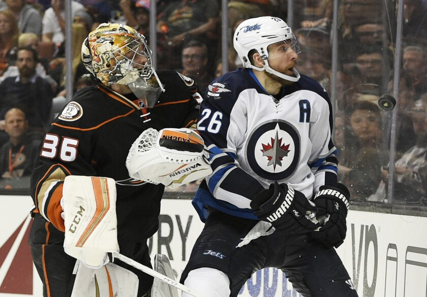 Jets forward Blake Wheeler, right, knocks the puck up and away from Ducks goalie John Gibson during the third period of a game on April 5.