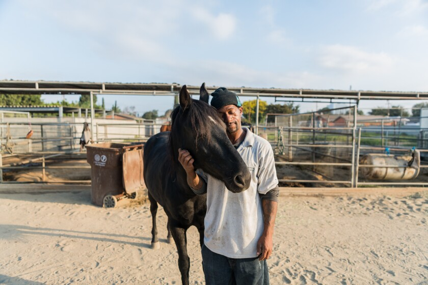 Anthony, a member of the Compton Cowboys, is having a moment with his horse, Dakota, on the Richland Farms ranch.