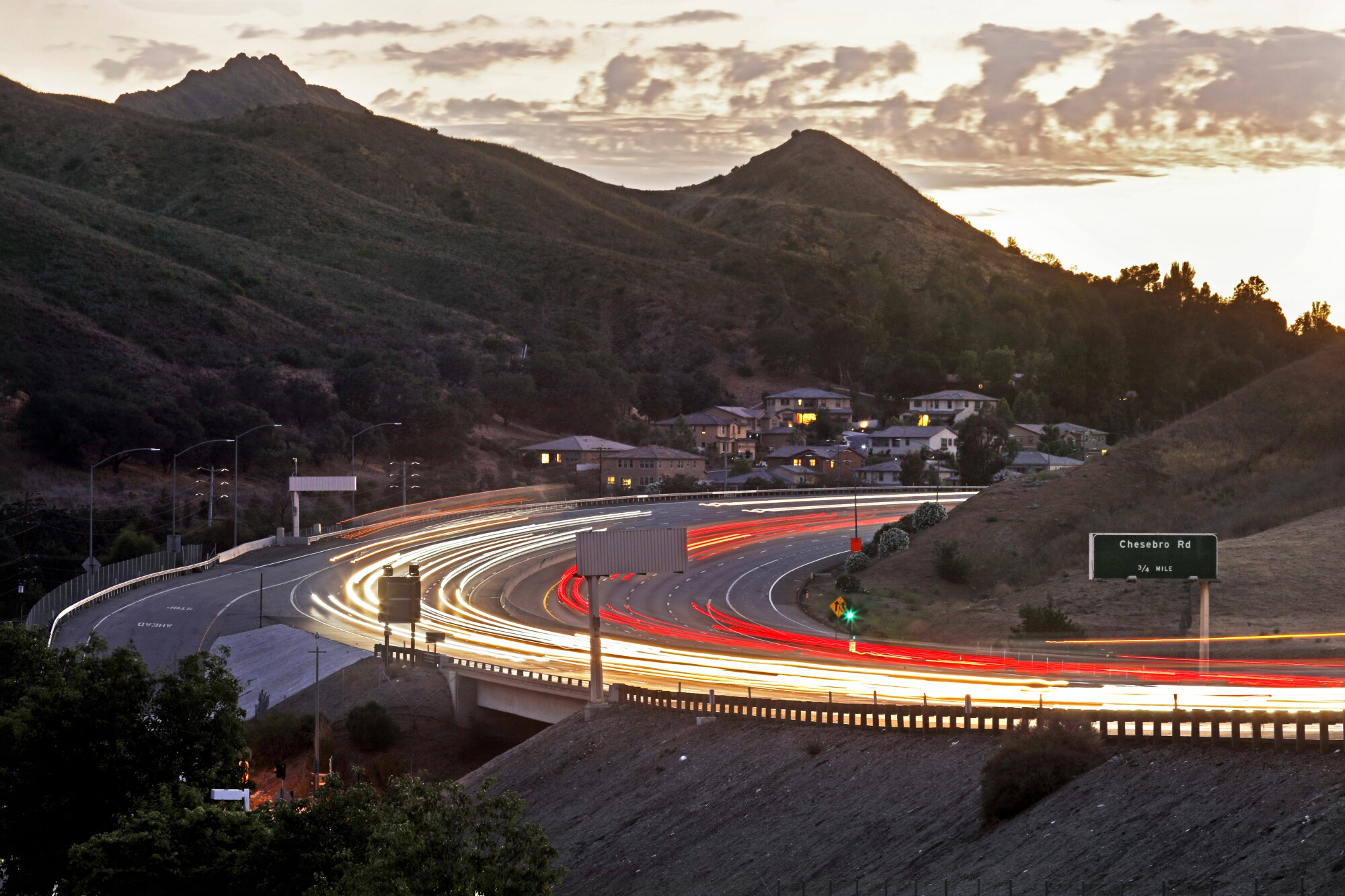 An aerial view captures ribbons of headlights and taillights on the 101 Freeway in Agoura Hills