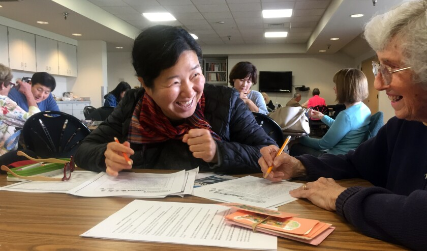 Volunteer English tutor Joyce Hartman, 87, right, shares a laugh with her student, Heejung Kim, who moved to North County two years ago from her native South Korea.