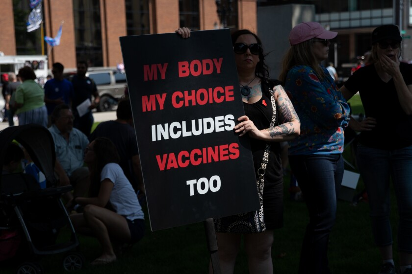 """Amid a crowd, a woman stands holding a sign that says """"My body my choice includes vaccines too."""""""