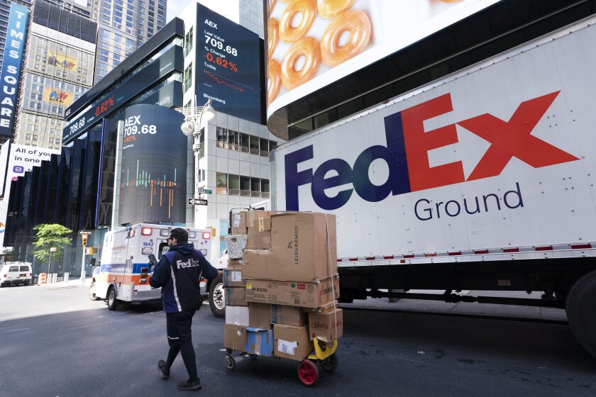 FILE - In this Thursday, May 6, 2021, file photo a FedEx driver delivers a cart of packages, in New York. Package delivery companies like FedEx have been in high demand during the pandemic, as more people stayed home and shopped online. At the same time, FedEx has been delivering COVID-19 vaccines. (AP Photo/Mark Lennihan, File)