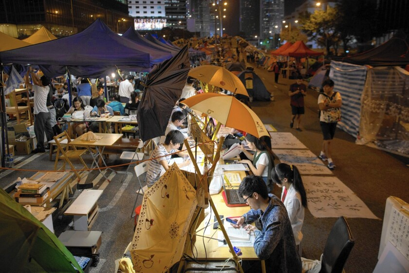 Students catch up on their studies at a protest site in Hong Kong this week. The city's tycoons appear to share protesters' concerns about economic disparity.