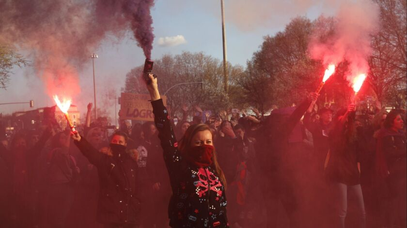 Women march holding flares during the International Women's Day in Madrid, Spain, Friday, March 8, 2