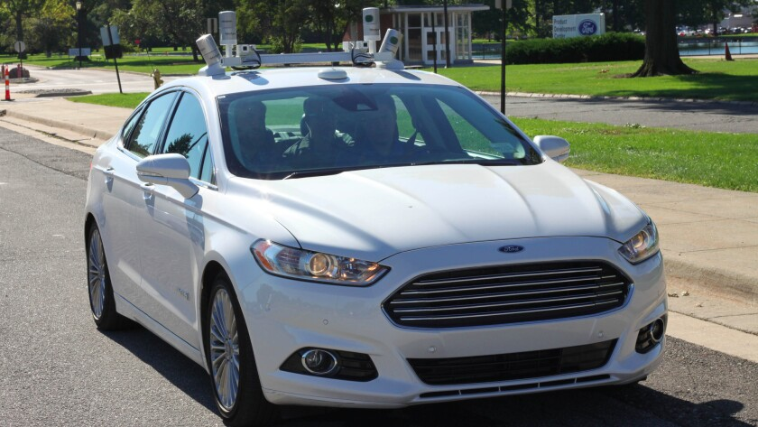 An experimental Ford Fusion autonomous car, lidar sensors on the roof, drives itself in Dearborn, Mich. on Sept. 12