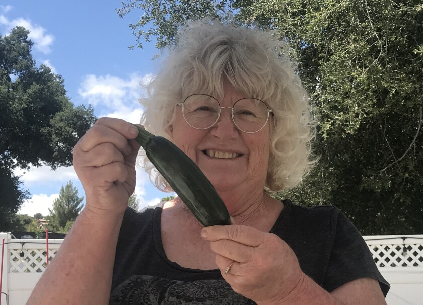 Christine Phillips with the first zucchini she grew in her backyard raised beds as COVID restrictions kept her at home.