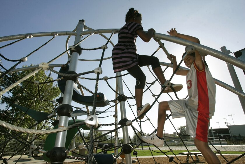 Celine McIntyre and her brother, Alec, of San Marcos, play at the San Marcos Civic Center Park.