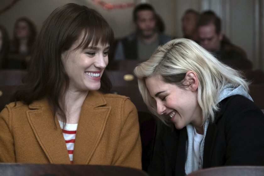 "This image released by Hulu shows Mackenzie Davis, left, and Kristen Stewart in a scene from ""Happiest Season."" (Hulu via AP)"