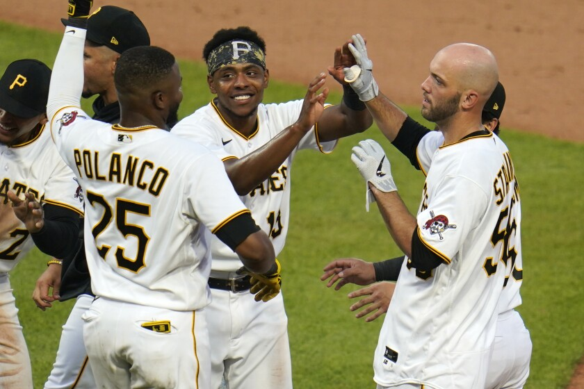 Pittsburgh Pirates' Jacob Stallings, right, celebrates teammates after driving in a run with a walkoff-single off Miami Marlins relief pitcher Adam Cimber during the 12th inning of a baseball game in Pittsburgh, Saturday, June 5, 2021. (AP Photo/Gene J. Puskar)