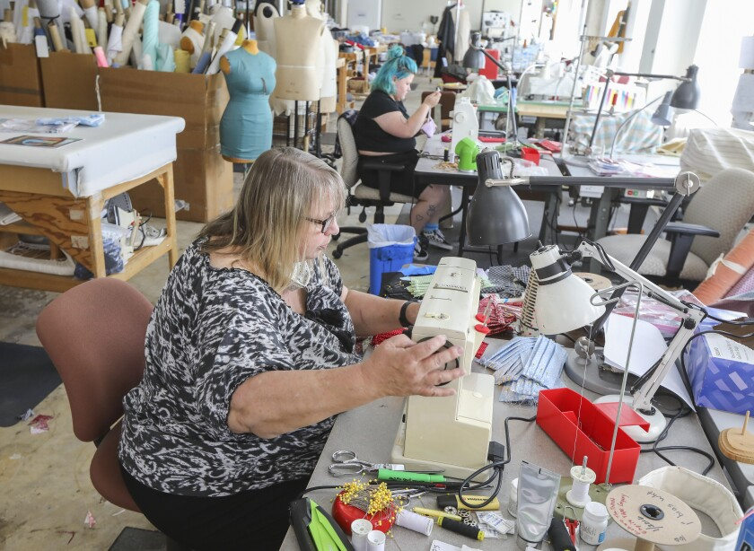San Diego Opera costume shop manager Ingrid Helton, foreground, and her daughter Delpha Hanson, background, make face masks for the needy at the Opera's costume shop on May 7 in downtown San Diego.