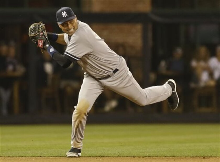 New York Yankees shortstop Derek Jeter tries to get a grip on the ball after fielding a hard grounder hit by San Diego Padres' Nick Hundley in the seventh inning of a baseball game in San Diego, Friday, Aug. 2, 2013. Jeter threw to second but the throw was wide. (AP Photo/Lenny Ignelzi)
