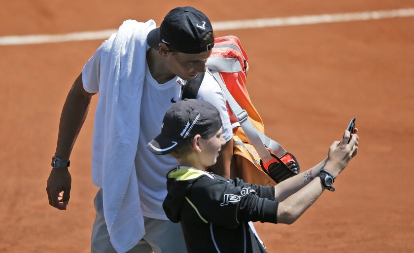 Defending champion Spain's Rafael Nadal poses for a selfie with an unidentified boy after a  training session for the French Tennis Open at the Roland Garros stadium, Friday, May 22, 2015 in Paris. The French Open starts Sunday. (AP Photo/Francois Mori)