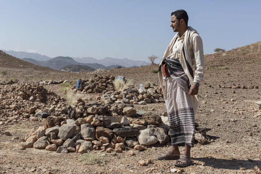 Ahmad Dabisi, who smuggles migrants from Yemen to Saudi Arabia, in a small cemetery where some of his clients lie buried.