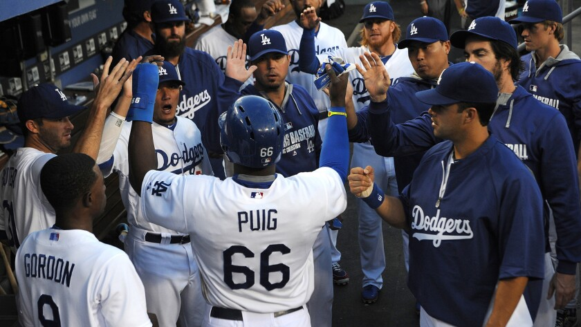Dodgers center fielder Yasiel Puig is congratulated by his teammates after scoring against the Atlanta Braves on July 31. Strife in the clubhouse doesn't matter as long as the Dodgers are winning.