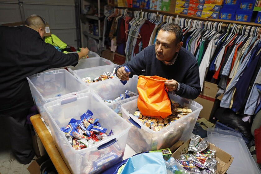 Mike Benavides, left, and Sergio Cordova prepare snack bags at their Brownsville home.