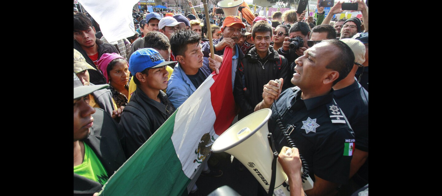 A Mexican federal police officer tells Central American migrants, who marched from a shelter to the border crossing in order to apply for asylum in the United States, that it's futile to do so because asylum request doesn't get processed at the footbridge crossing.