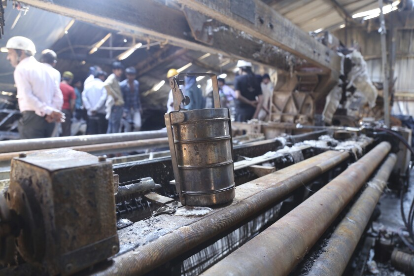 In this Sunday, Feb. 9, 2020 photo, a tiffin carrier belonging to a worker lies amid charred remains after a fire broke out at Nandan Denim, one of the world's largest denim suppliers, in Ahmedabad, India. At least seven people died in the blaze that swept the factory that has ties to major U.S. retailers, according to its website. Some of the U.S. and multinational companies listed on the website said they were not actually customers, and many issued statements that strongly condemned dangerous work sites. (AP Photo)