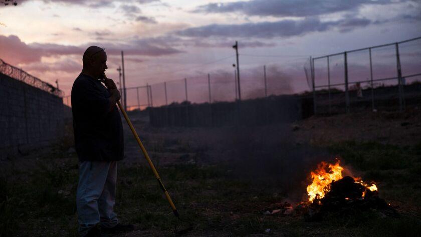 A man burns trash near the border fence in the Anapra neighborhood of Ciudad Juarez, Mexico, late We
