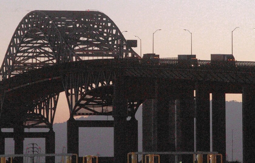 Three trucks cross the Gerald Desmond Bridge in Long Beach. A string of actions by state officials and the National Labor Relations Board has strengthened the hand of truck drivers who say they need union representation to improve pay and working conditions.