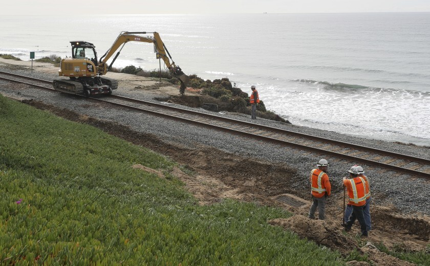 Workers on Saturday, Nov. 30, repair an area next to the railroad tracks in Del Mar that washed out during last week's storm.