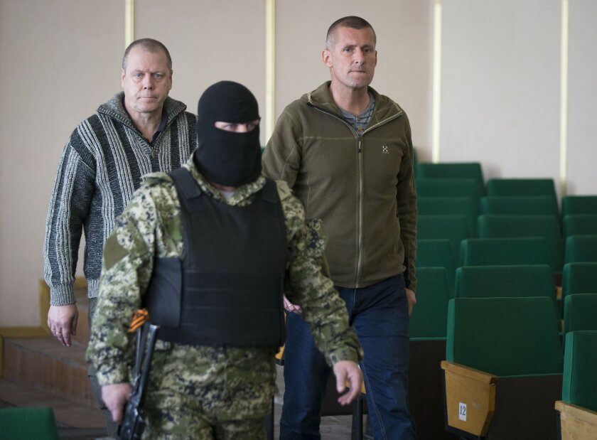 John Christensen, right, a senior Sgt. in the Danish army and his colleague, both members of a group of foreign military observers are escorted by a pro-Russian militant to attend a press conference in the city hall of Slovyansk, eastern Ukraine, Sunday, April 27, 2014. As Western governments vowed to impose more sanctions against Russia and its supporters in eastern Ukraine, a group of foreign military observers remained in captivity Saturday accused of being NATO spies by a pro-Russian insurgency. The German-led, eight-member team was traveling under the auspices of the Organization of Security and Cooperation in Europe when they were detained Friday. (AP Photo/Alexander Zemlianichenko)