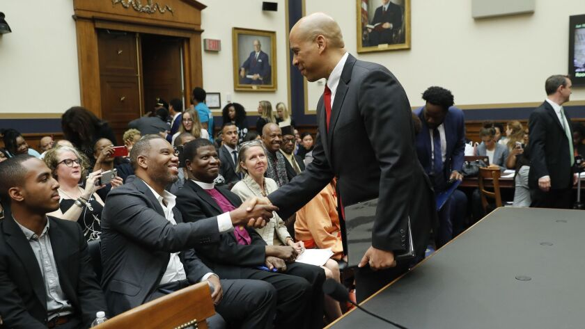 Sen. Cory Booker (D-N.J.), right, shakes hands with author Ta-Nehisi Coates in Washington as he waits to testify on June 19 about reparations for the descendants of slaves.