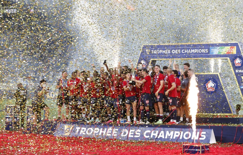 Lille's players celebrate on the podium after winning the French Super Cup final soccer match between Lille and Paris Saint-Germain at Bloomfield Stadium in Tel Aviv, Israel, Sunday, Aug. 1, 2021. (AP Photo/Ariel Schalit)