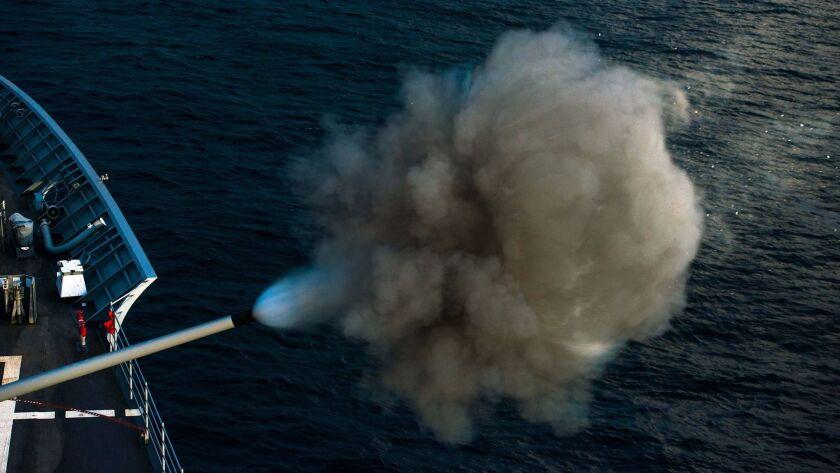 The Navy cruiser Bunker Hill fires an MK-45 5-inch gun during an air defense exercise off the coast