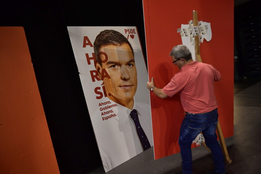 In this photo taken on Friday, Nov. 1, 2019, a worker moves portraits of Spanish socialist candidate Pedro Sanchez ahead of a campaign rally in Pamplona. Spain is holding its fourth general election in as many years amid voter distrust and a renewed Catalan independence bid that has bolstered the far right. (AP Photo/Alvaro Barrientos)