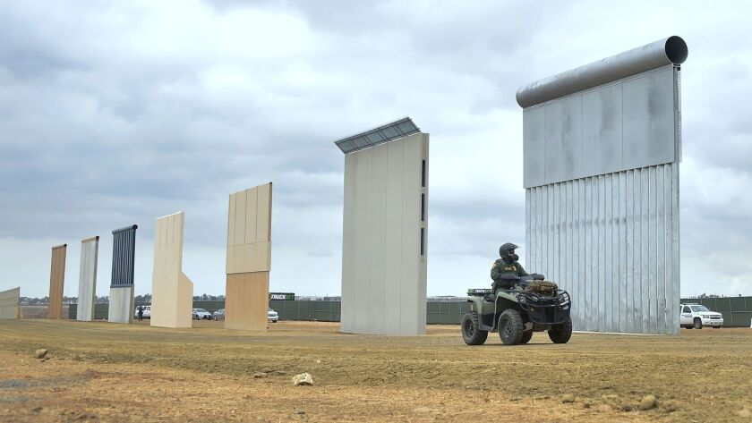 A border patrol officer rides past prototypes of President Trump's proposed border wall in San Diego.