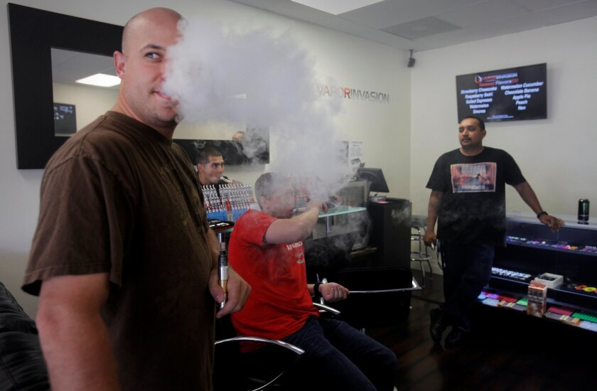 Joshua Kirkpatrick, left, lets out a stream of e-cigarette vapor, while in the background, Vapor Invasion employee Carlos Cardenas, behind the bar, talks with customers Brad Martini and Darin Bandhu, right. =At Vapor Invasion, on a Sunday afternoon, customers gathered and talked about flavors, the