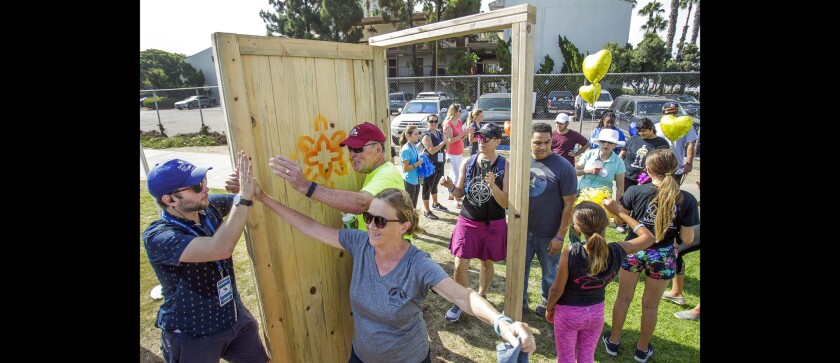 In this photo from 2018, Barbara and Harry Melkerson high-five Matt Bezroch as they walk through a door symbolizing the creation of affordable housing during the annual A Short Walk Home event. Father Joe's Villages is holding this year's event to raise awareness of homelessness Saturday at Spanish Landing Park.