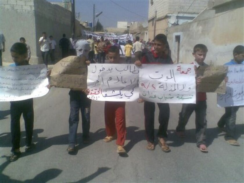 "In this citizen journalism image made on a mobile phone and provided by Shaam News Network, anti government protesters hold Arabic placards reading:""The Friday of Death Rather Than Humiliation"", center right, and ""We want the free media to enter and reveal the truth"", center left,during a demonstration against the Syrian regime, at Andan village, in Aleppo province, Syria, on Friday Sept. 2, 2011. Syria faced international calls for tougher sanctions as anti-government protesters vowed Friday they will choose death over humiliation at the hands of the regime. (AP Photo/Shaam News Network) EDITORIAL USE ONLY, NO SALES, THE ASSOCIATED PRESS IS UNABLE TO INDEPENDENTLY VERIFY THE AUTHENTICITY, CONTENT, LOCATION OR DATE OF THIS HANDOUT PHOTO"